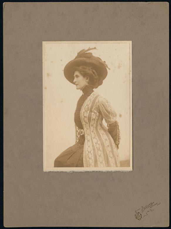 Vue de profil de Madge Macbeth portant une robe noire avec une veste de dentelle et un chapeau orné de plumes.