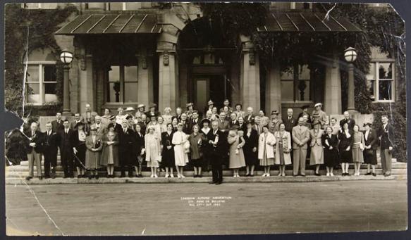 Grand groupe de femmes et d'hommes debout devant la porte d'entrée d'un bâtiment.