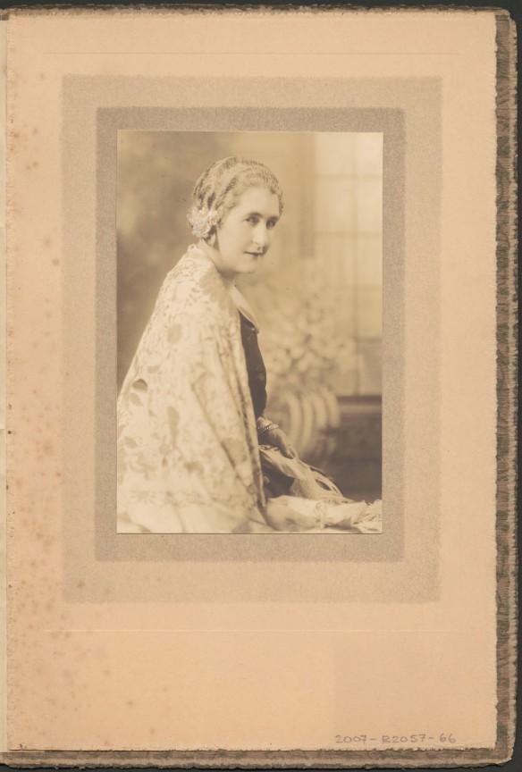 Portrait de Madge Macbeth vue de profil, vêtue d'une cape à motifs de couleur pâle.