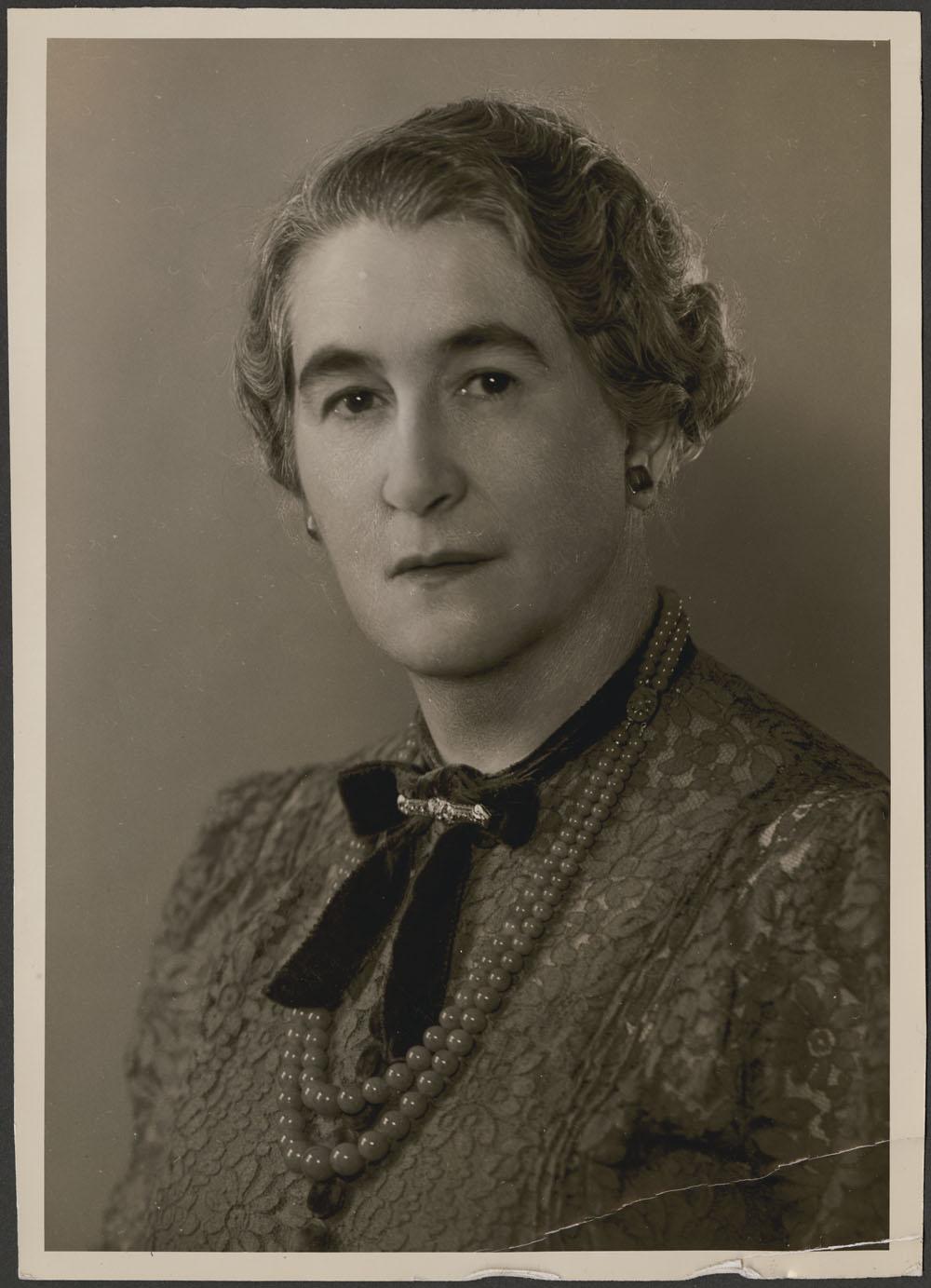 Photographie de type portrait d'une femme portant un chemisier en dentelle, un collier de perles de jade et une broche en diamant, et regardant l'appareil photo.