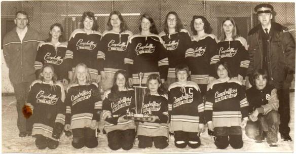 Photographie sépia d'une équipe de jeunes hockeyeuses portant un chandail où l'on peut lire « Campbellford Minor Hockey ».