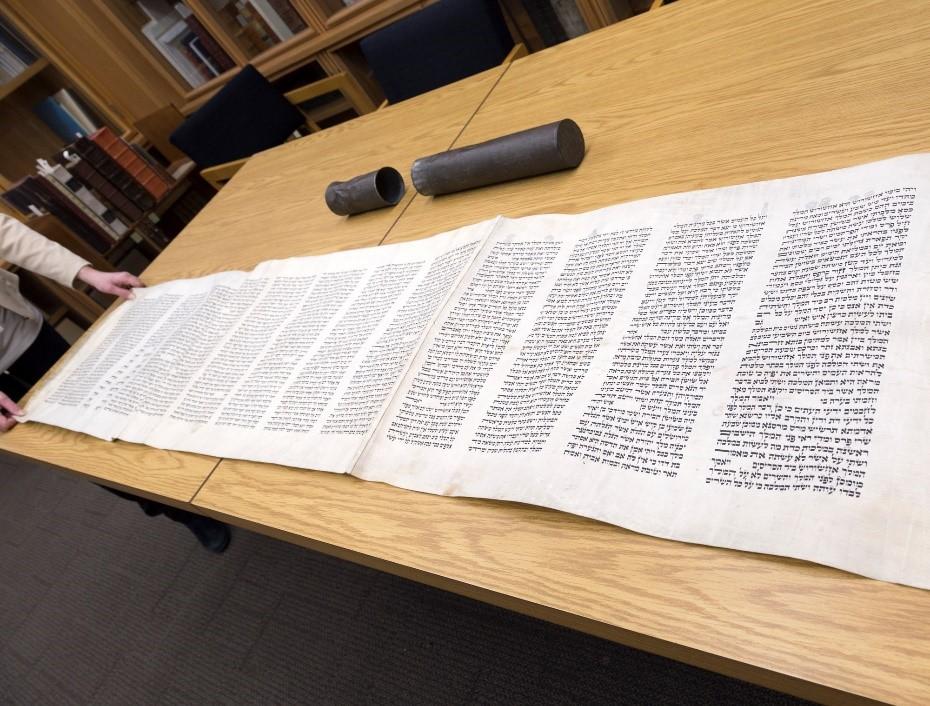 Une photographie couleur d'un manuscrit hébraïque rédigé sur un parchemin d'une longueur approximative de sept pieds, entièrement déroulé sur une table. L'étui en métal qui contenait le manuscrit se trouve aussi sur la table.