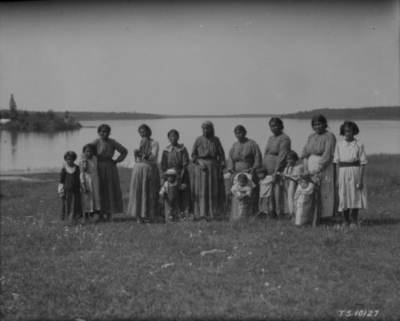 Photographie noir et blanc de sept femmes, sept enfants et une adolescente sur la rive d'un lac. Deux des enfants sont dans des tikinagans.
