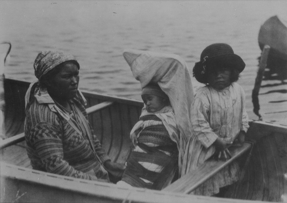 Photographie noir et blanc d'une femme et de deux enfants dans un canot. Un des enfants est endormi dans un tikinagan.
