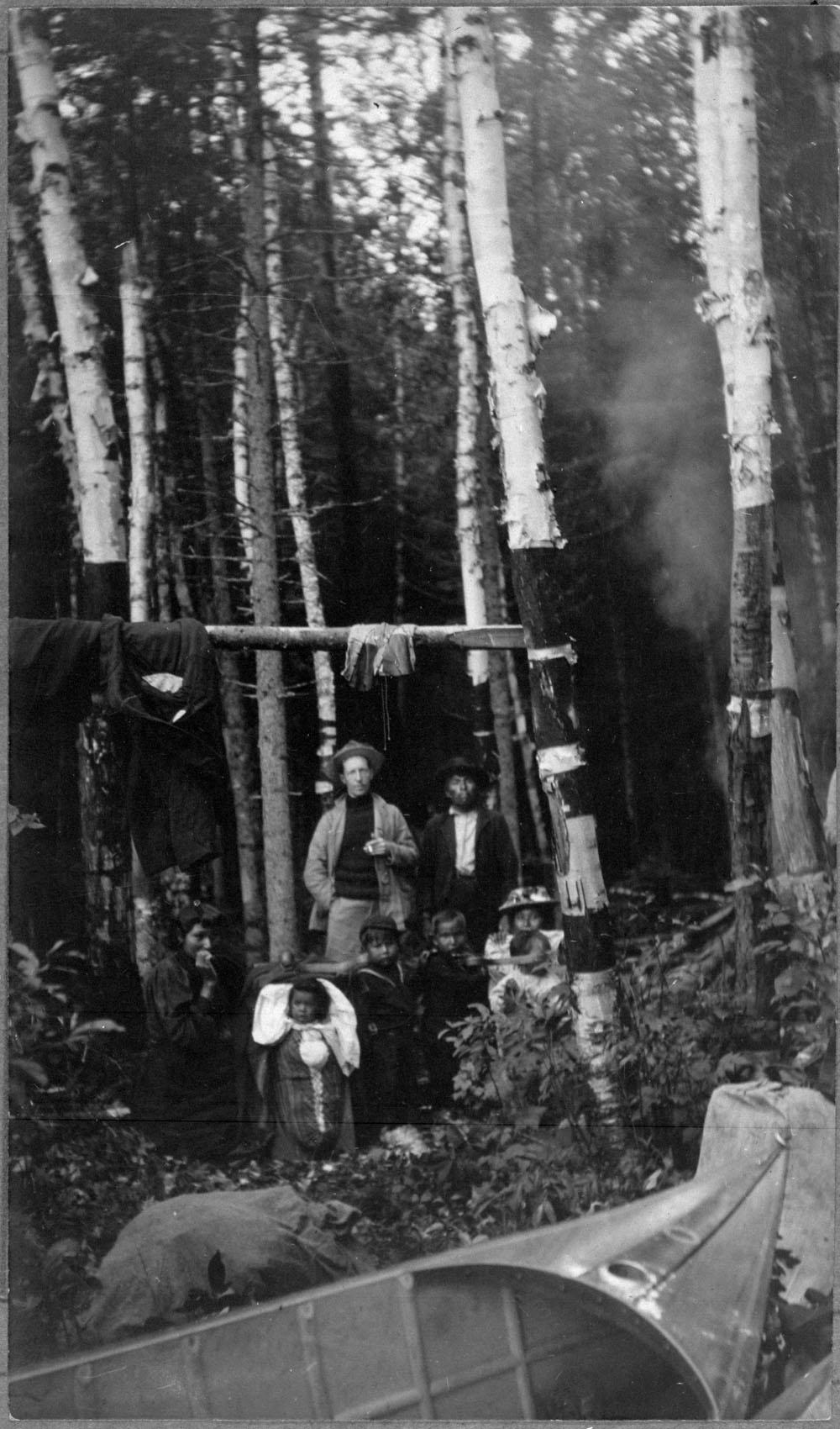 Photographie noir et blanc de huit personnes en forêt, dont un bébé dans un tikinagan. On voit un canot à l'avant-plan.