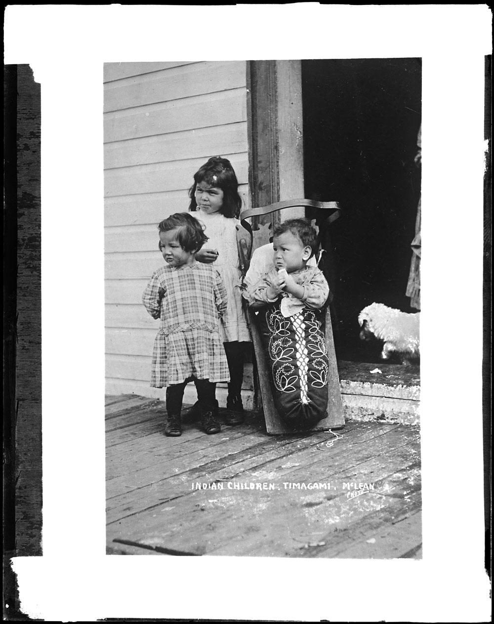 Photographie noir et blanc de trois enfants. Le plus jeune est installé dans un tikinagan au motif de broderie fleurie.