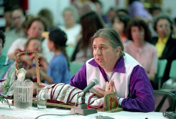 Photographie couleur d'un homme portant une chemise blanche et mauve assis à une table et parlant dans un microphone. Devant lui sur la table, un bébé est couché dans un tikinagan dont le tissu est blanc et rouge.