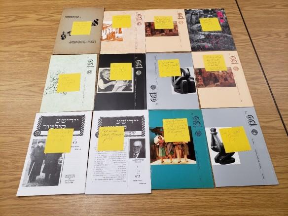 Douze périodiques déposés sur une table. Chaque numéro comporte un papillon adhésif sur lequel Goldie Morgentaler a identifié le contenu canadien.