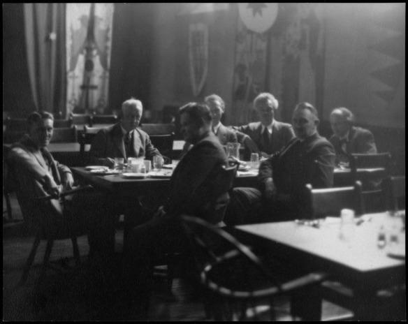 Photo noir et blanc de sept hommes vêtus de complets assis autour d'une table durant un repas.
