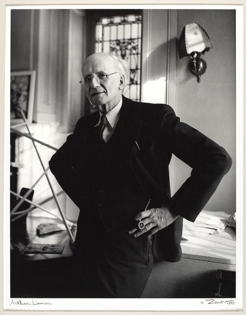 Photo noir et blanc d'un homme debout, la main gauche reposant sur sa hanche avec une pipe dans la main