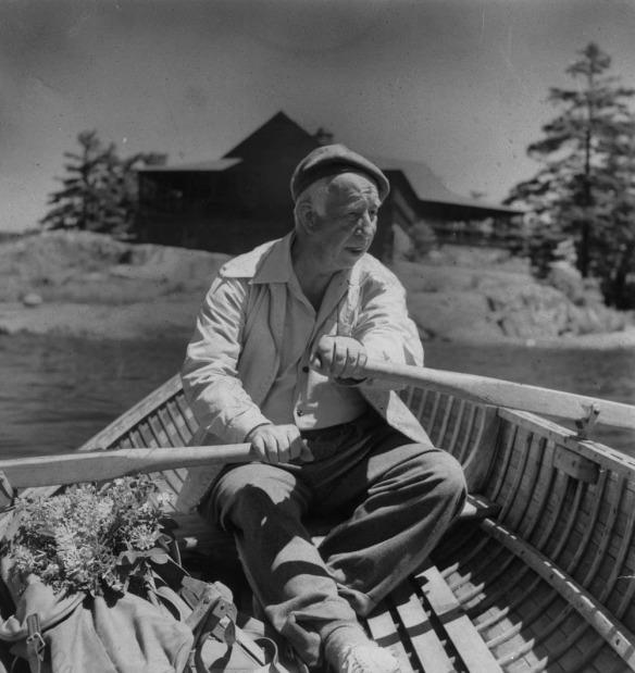 Photo noir et blanc d'un homme ramant dans un canot en bois.