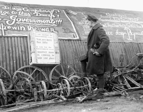 Photo noir et blanc d'un soldat en uniforme, lisant une affiche de propagande sur laquelle est écrit : « Un vote contre le gouvernement : vous restez ici pour toujours. Un vote pour le gouvernement : un autre homme prendra votre place ». [Traduction]