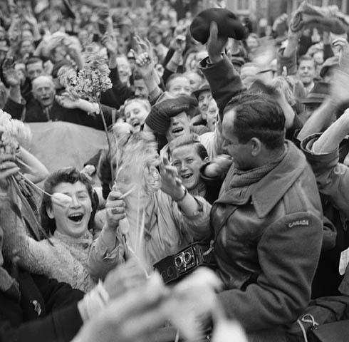 Une foule de gens avec les bras levés, dont une jeune femme tenant des tulipes dans ses mains, entourant un soldat canadien brandissant son chapeau.