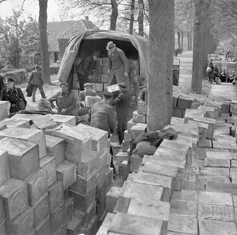Plusieurs personnes sortent des caisses de vivres de l'arrière d'un camion militaire. De nombreuses caisses sont empilées au premier plan.