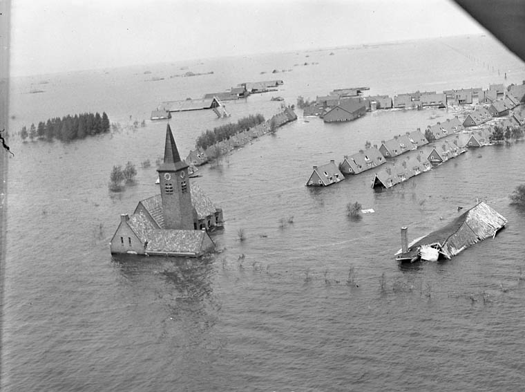 Village inondé dont les toits de maisons et le clocher de l'église émergent de l'eau.