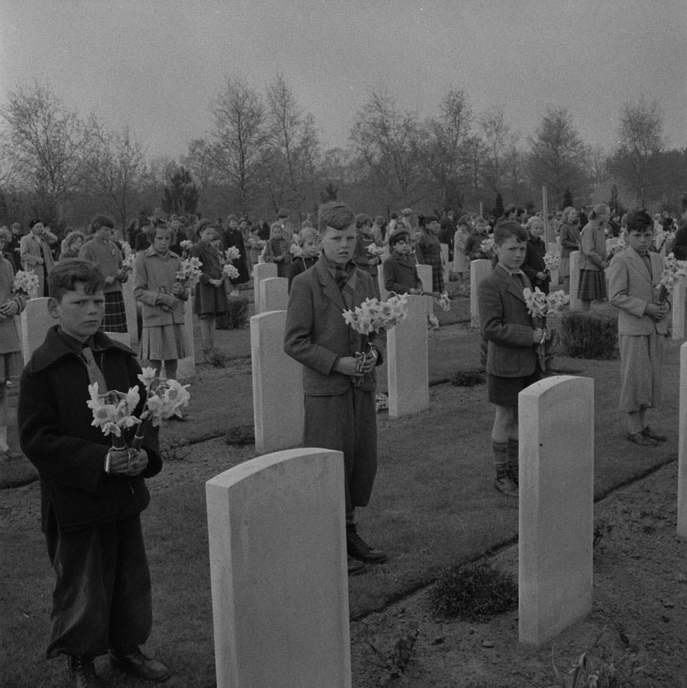 De nombreux enfants debout devant des pierres tombales, tenant des bouquets de jonquilles.