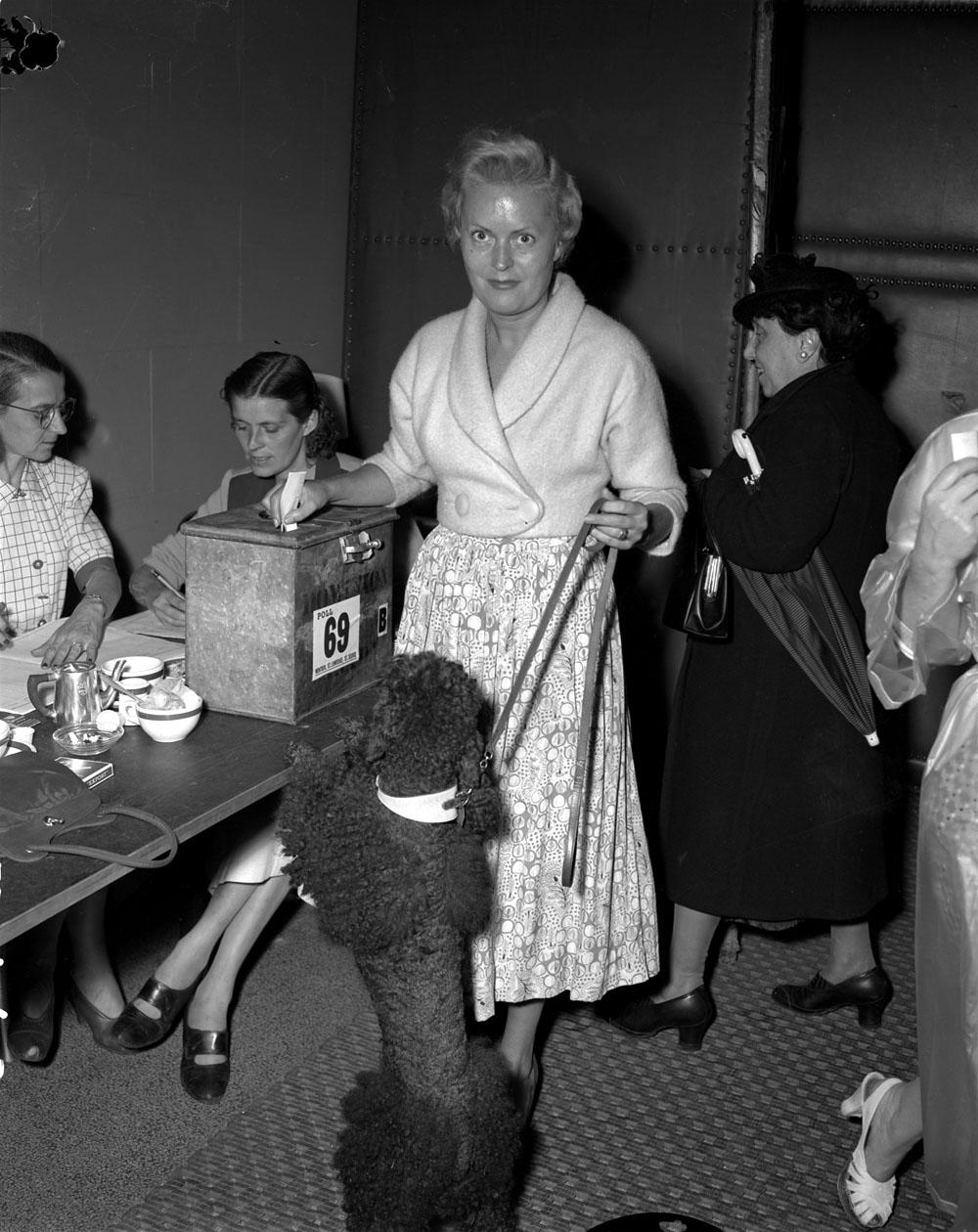 Photo noir et blanc d'une femme souriante, tenant son chien en laisse et déposant son bulletin de vote dans une boîte de scrutin. À l'arrière-plan, d'autres femmes attendent pour voter, tandis que deux femmes vérifient la liste électorale.