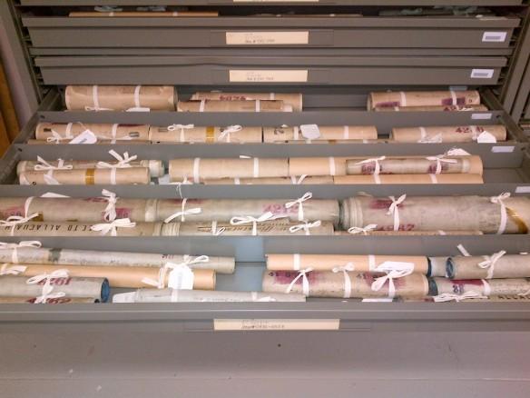 Photo couleur de cartes enroulées, attachées avec un ruban écru.
