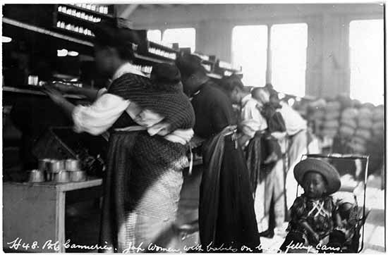 : Photographie noir et blanc de quatre femmes travaillant sur la chaîne de production d'une conserverie de poisson. Deux d'entre elles ont leur bébé attaché sur leur dos dans une écharpe. Un enfant est assis dans une poussette derrière elles.