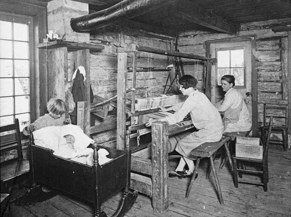 Photographie noir et blanc de deux femmes assises sur des bancs dans une cabane en bois rond. Elles travaillent à un grand métier à tisser, pendant qu'un jeune enfant s'occupe d'un bébé couché dans un berceau à leurs côtés.