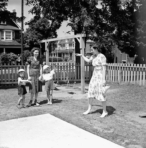 Photographie noir et blanc d'une mère saluant ses deux jeunes enfants, qui tiennent la main de leur éducatrice. La garderie semble être située sur un terrain clôturé, dans un quartier résidentiel. À l'arrière-plan figure un module avec des balançoires.