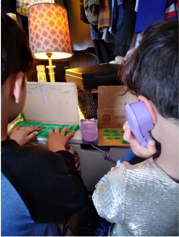 Photographie couleur de deux jeunes enfants de dos, assis à une table dans un espace encombré. Ils jouent à travailler en tapant sur des « ordinateurs » bricolés en carton et en parlant dans un téléphone en plastique.