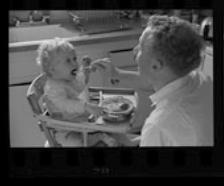 Un père fait manger son enfant, qui est assis dans une chaise haute, dans la cuisine. La bouche ouverte, il imite son enfant.