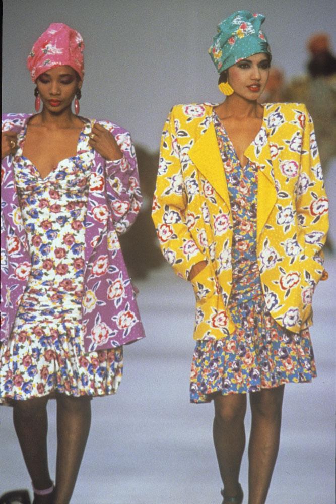 Une photographie couleur de deux femmes défilant sur un podium, vêtues d'une robe, d'une veste et d'un turban en coton imprimé.