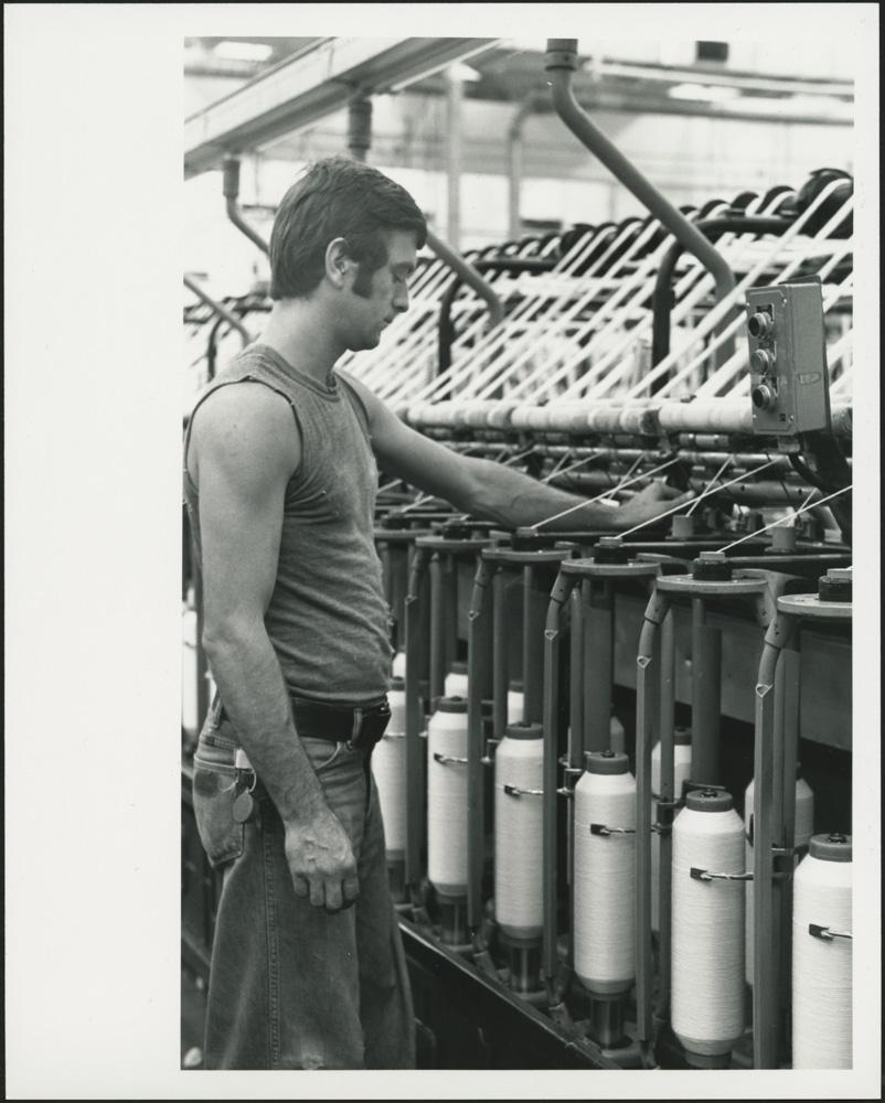 Une photographie noir et blanc d'un homme portant un jean et un chandail sans manches et surveillant une machine à bobiner.