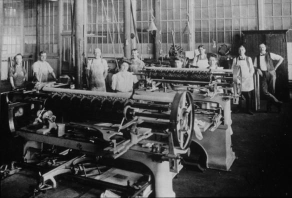 Une photographie noir et blanc montrant des hommes et des femmes posant dans une usine, de grosses machines au premier plan.
