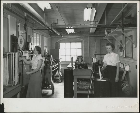 Une photographie noir et blanc de deux femmes debout, utilisant des appareils dans un laboratoire; il y a une large fenêtre à l'arrière-plan, et des tuyaux et des lampes fluorescentes au plafond.