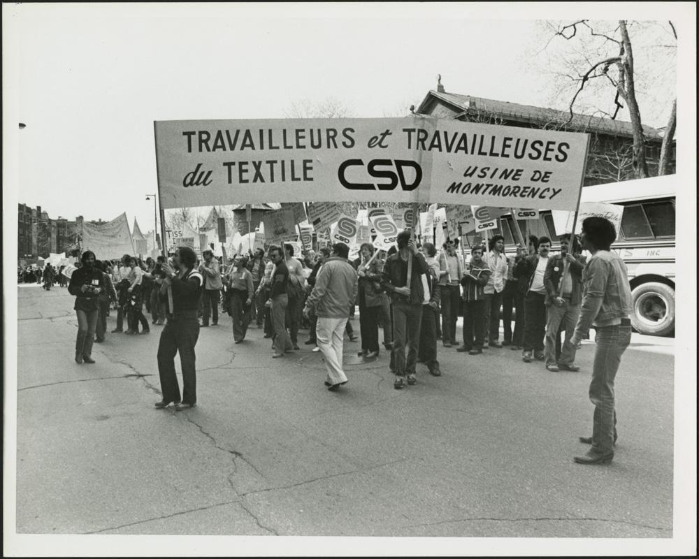 Une photographie noir et blanc d'un groupe de personnes marchant dans la rue et portant une bannière sur laquelle est écrite : «Travailleurs et travailleuses du textile, CSD [Centrale des syndicats démocratiques], usine de Montmorency».