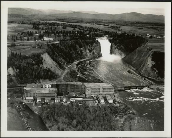 Une photographie aérienne noir et blanc montrant une usine près d'une rivière, avec une imposante chute à l'arrière-plan.