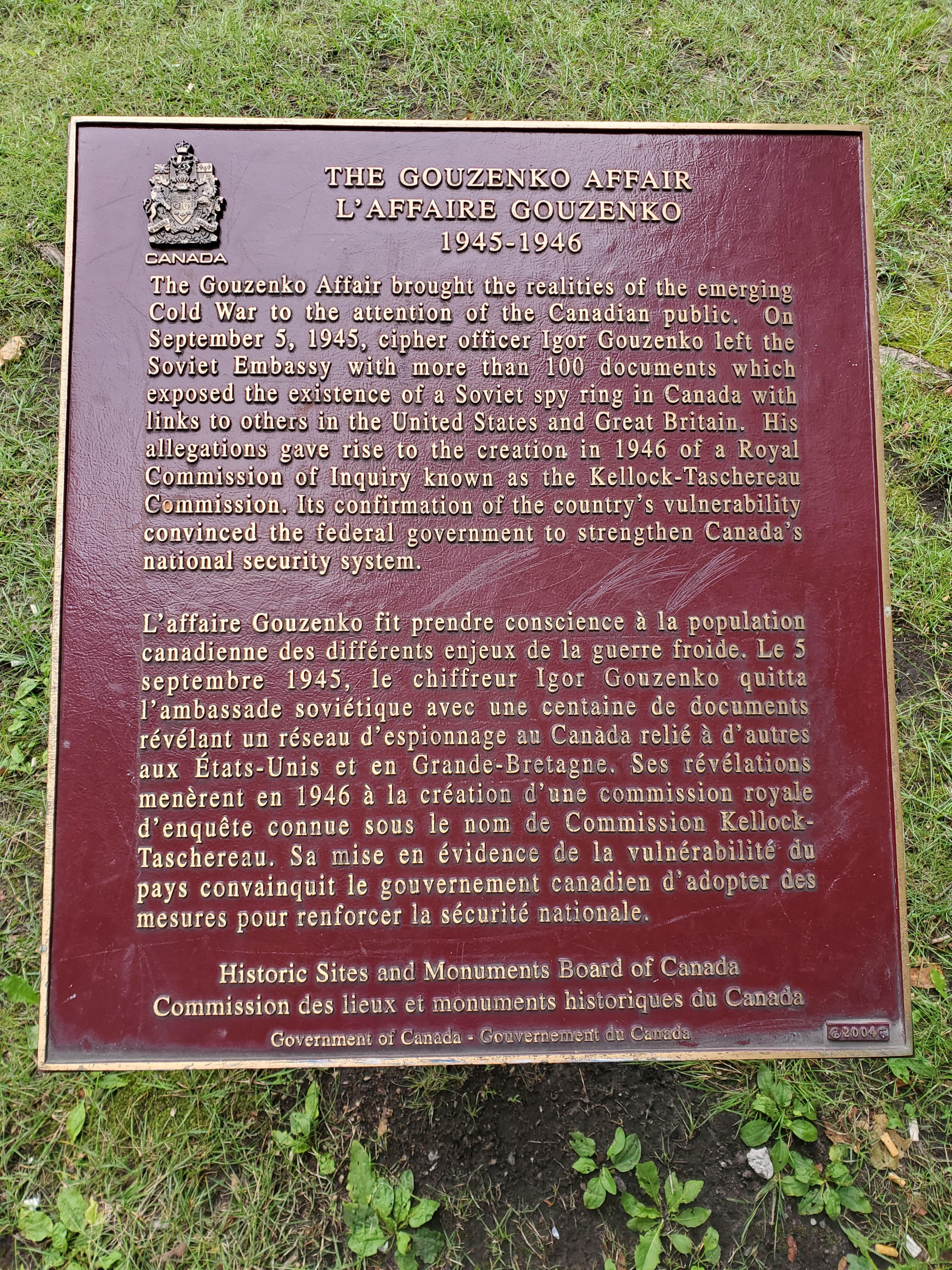 Une plaque rouge avec des écritures dorées et les armoiries du Canada dans le coin supérieur gauche.