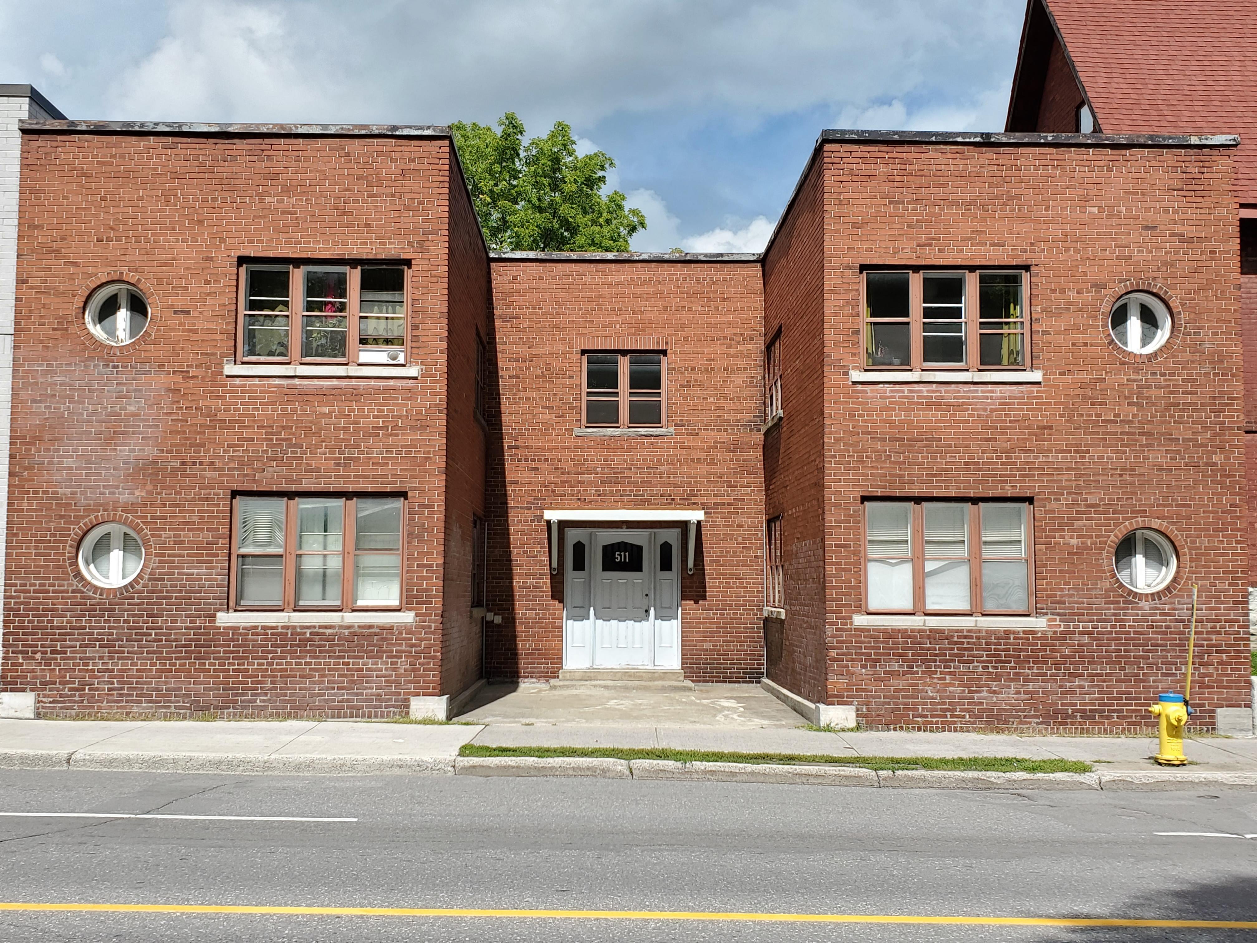 Une photo couleur d'un immeuble résidentiel en briques brunes avec une porte blanche.