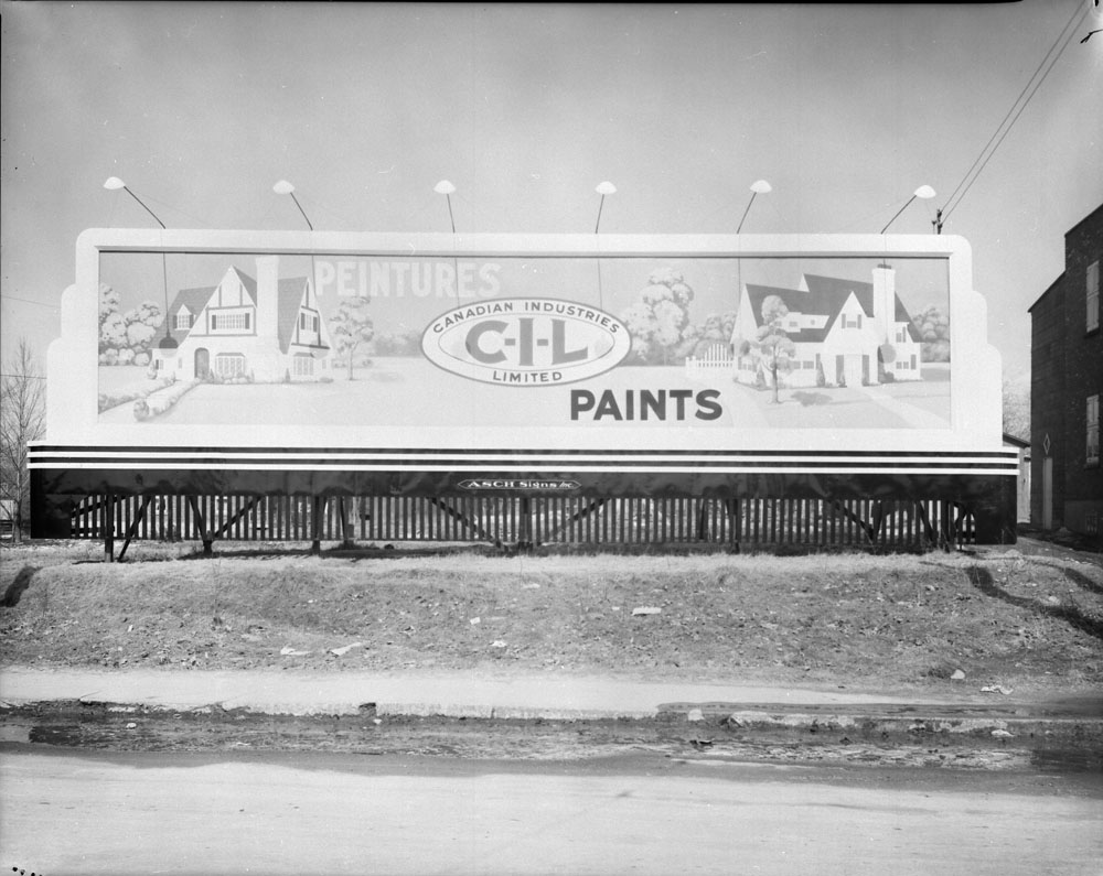 Photographie noir et blanc montrant un grand panneau de forme rectangulaire ancré dans un talus et affichant une publicité de la compagnie CIL. La publicité prend la forme d'une œuvre peinte, avec une maison à chaque extrémité, le tout situé dans un paysage de banlieue. Entre les deux maisons, on aperçoit le logo ovale de la compagnie CIL, avec les mots « Peintures » en haut à gauche et « Paints » en bas à droite.