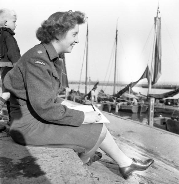 Photo noir et blanc montrant une femme en uniforme, assise sur un quai, vue de côté. Elle tient une tablette à dessin et un crayon, et elle sourit. En arrière-plan, on voit un enfant blond ainsi que des voiliers amarrés au quai.