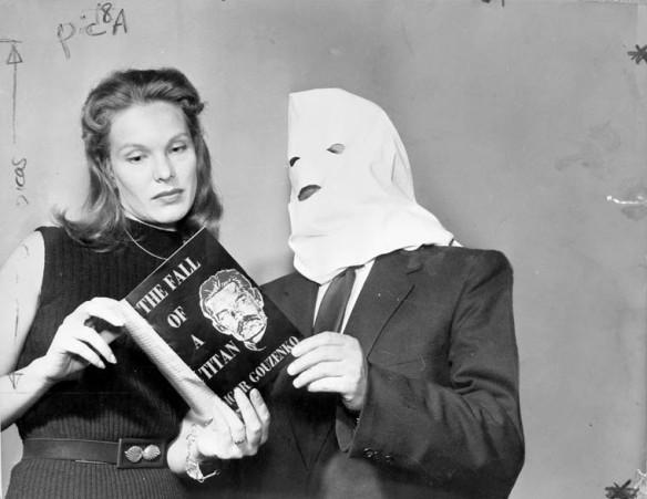 Photo noir et blanc d'une femme et d'un homme, une capuche lui recouvrant le visage, regardant un livre intitulé The Fall of a Titan. Sur la couverture, on voit une photo de Joseph Stalin et le nom de l'auteur, Igor Gouzenko.