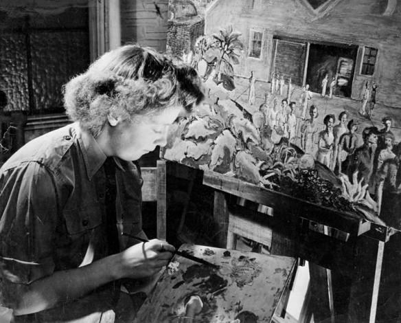 Photo noir et blanc, prise de côté, montrant Molly Lamb Bobak en train de peindre devant un chevalet, un pinceau et une palette de couleurs à la main.