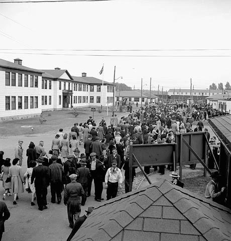 Photographie noir et blanc montrant des employés devant des bâtiments d'usine, s'éloignant de ce qui semble être un vestiaire. La plupart sont vus de dos; d'autres font face à la caméra ou discutent entre eux. On aperçoit en arrière-plan quelques wagons de train.
