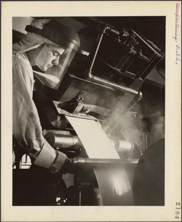 Photographie noir et blanc d'un travailleur portant un équipement de protection et une visière, versant d'une machine un liquide blanc coulant en une bande uniforme dans un cylindre qu'il tient de la main droite. Un peu de fumée s'échappe du liquide.