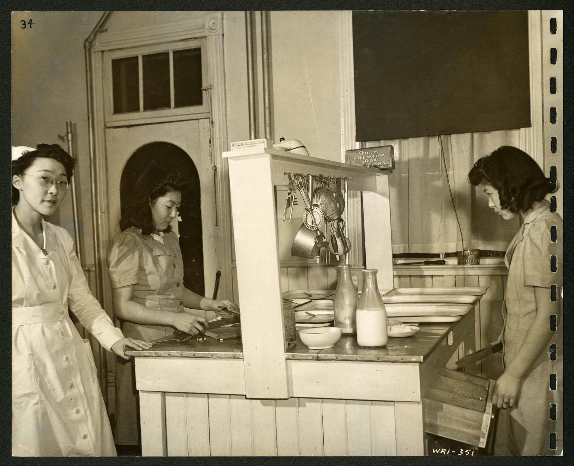 Trois femmes, dont une infirmière, se tiennent autour d'un îlot où se trouvent des cabarets, de la vaisselle et des bouteilles de lait. Des ustensiles sont suspendus au montant central de l'îlot.