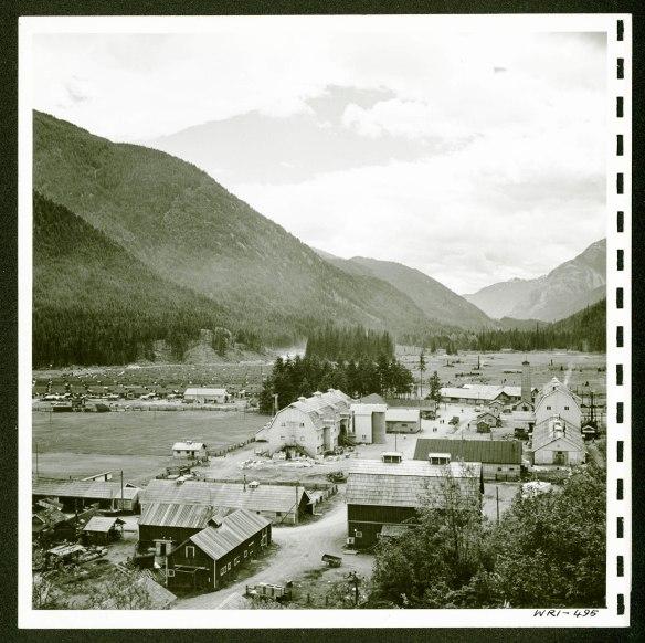 Un village environné de montagnes. On aperçoit plusieurs bâtiments à l'avant-plan et des rangées de plus petites habitations plus loin à gauche.