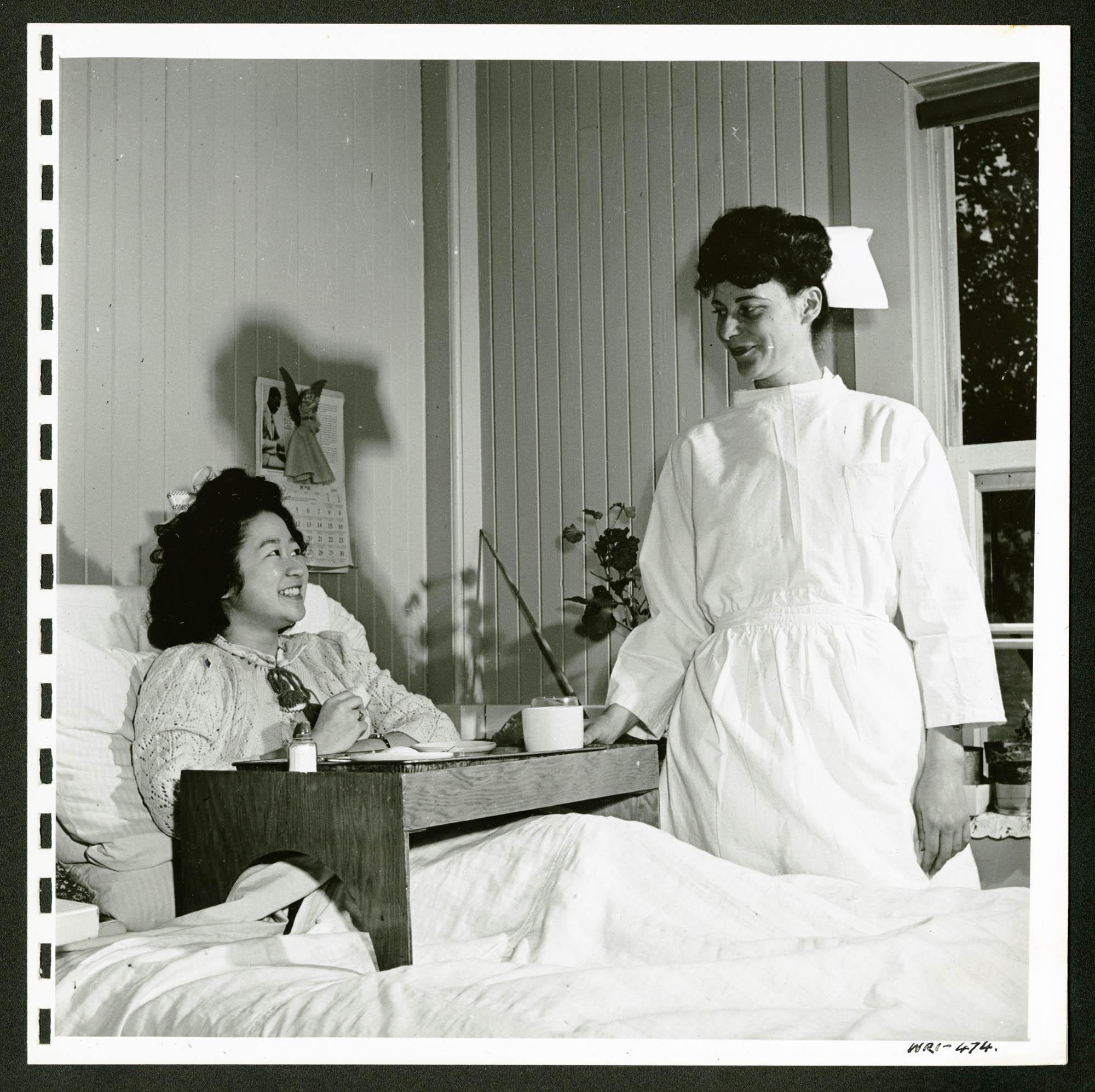 (de gauche à droite) Patiente alitée (et internée), avec une infirmière à son chevet.