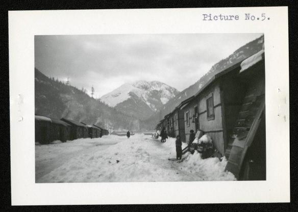 (de droite à gauche) Des enfants se tiennent devant leurs baraques en bois à feuillure, contre lesquelles on a pelleté la neige. Plus loin, une personne internée marche dans cette rue de fortune. Les murs des baraques sont recouverts d'un papier goudronné les protégeant des éléments.