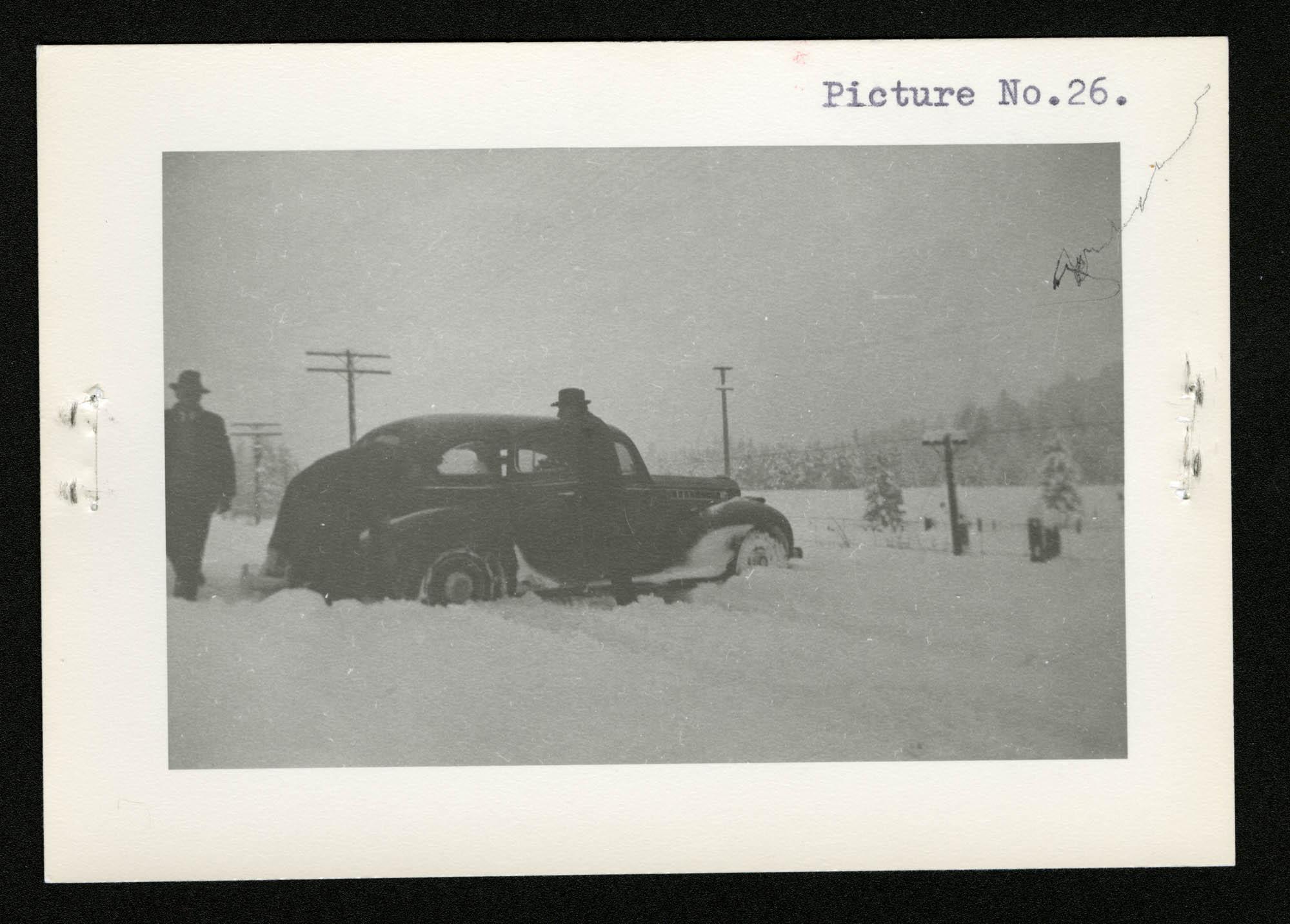 Trois hommes et une voiture dans une tempête de neige – (de droite à gauche) un homme est debout près de la portière, un deuxième est penché près de la roue arrière droite et un troisième vient les aider.