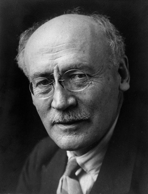 Photo noir et blanc montrant le visage d'un homme en gros plan. Il porte la moustache et de petites lunettes rondes.