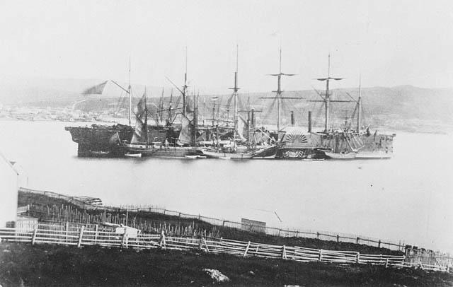 Photo noir et blanc d'un grand navire vu de la rive.