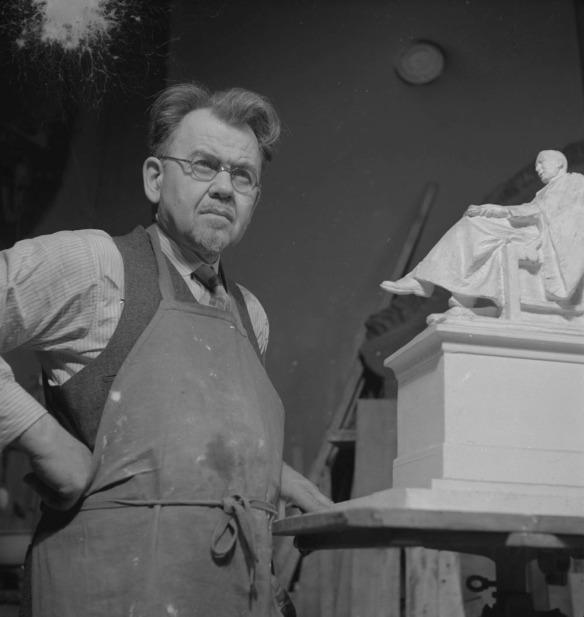 Photo noir et blanc montrant un homme portant un tablier, debout à côté d'un modèle d'une statue. Il porte des lunettes et tient un poing sur sa hanche.