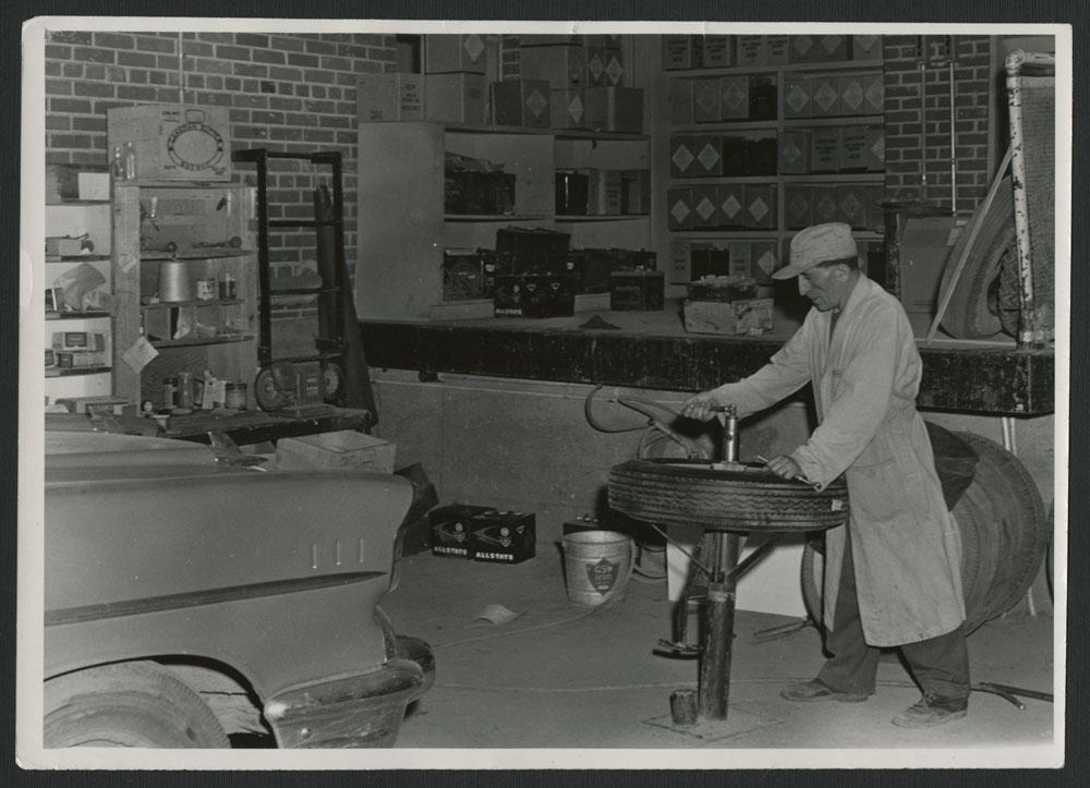 Photo noir et blanc d'un mécanicien vêtu d'un sarrau et d'une casquette, en train de travailler sur un pneu. On aperçoit un comptoir à l'arrière-plan et une voiture à l'avant-plan.
